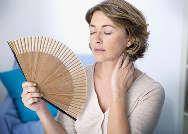 Menopausal woman experiencing symptoms and cooling herself with a fan