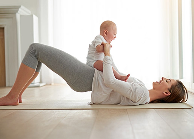 Mother with her toddler doing exercises on a yoga mat.