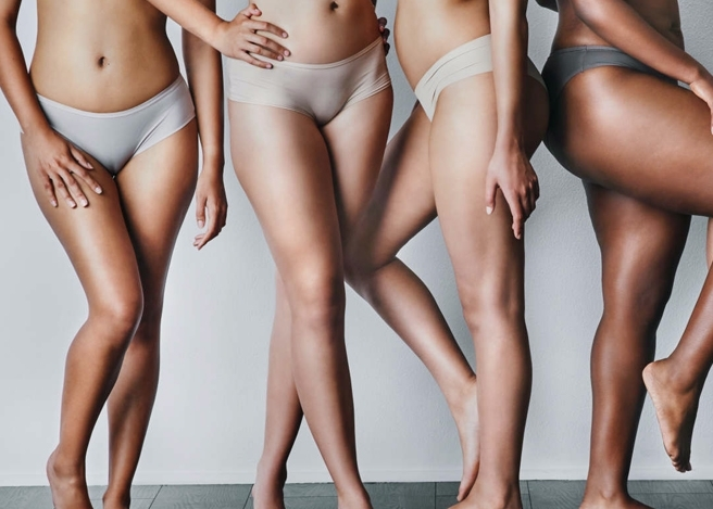 Multi racial women of all sizes standing together with clear smooth skin.